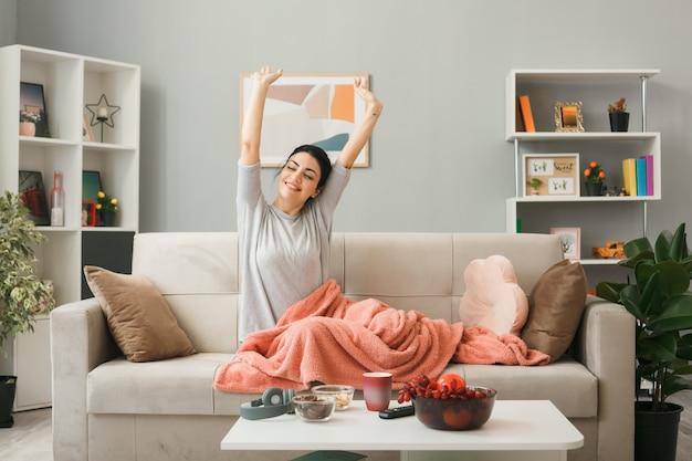 Sorridente ragazza avvolta in plaid allungando il braccio, seduta sul divano dietro il tavolino da caffè in soggiorno