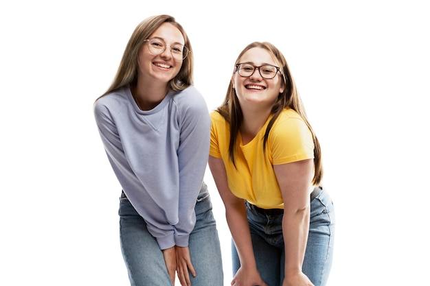 Smiling young girlfriends in glasses. love and tenderness. isolated on white wall.