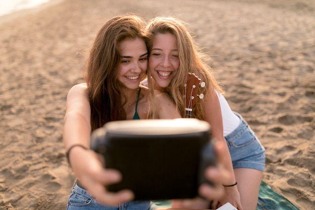 Smiling young girls taking self portrait from instant camera at beach