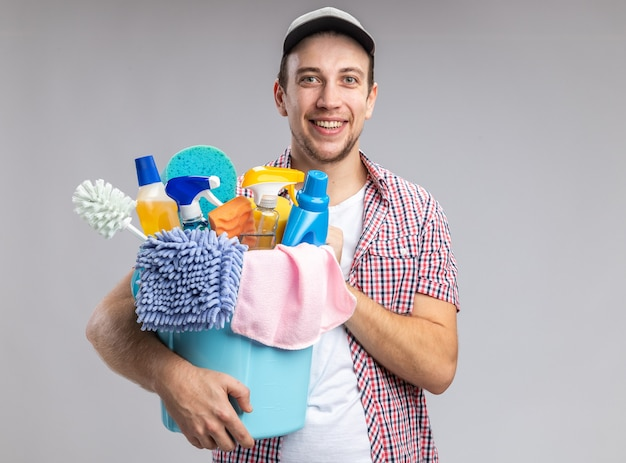 Smiling young guy cleaner wearing cap holding bucket with cleaning tools isolated on white background