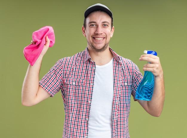 オリーブグリーンの背景で隔離のぼろきれと洗浄剤を保持しているキャップを身に着けている若い男クリーナーの笑顔