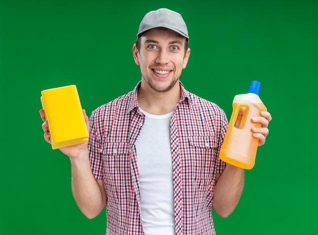 緑の背景に分離されたスポンジと洗浄剤を保持しているキャップを身に着けている若い男クリーナーの笑顔