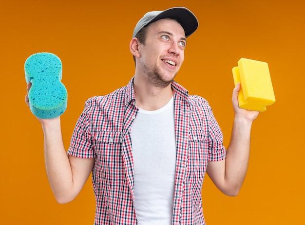 Sorridente giovane pulitore che indossa un cappuccio che tiene le spugne per la pulizia isolate su sfondo arancione