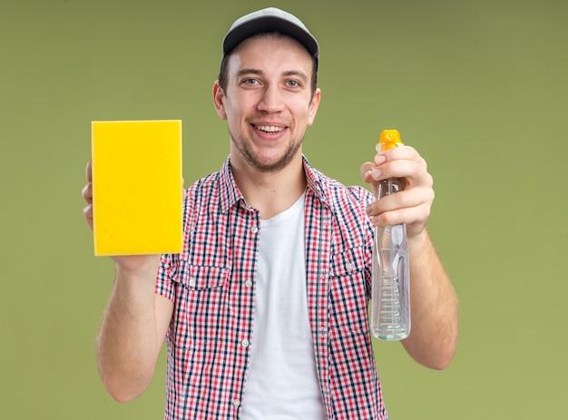 オリーブグリーンの壁に分離されたスポンジで洗浄剤を差し出すキャップを身に着けている若い男クリーナーの笑顔