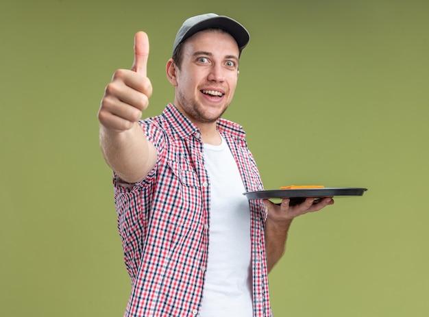 オリーブグリーンの背景で隔離の親指を示すトレイにスポンジを保持しているキャップを身に着けている若い男クリーナーの笑顔
