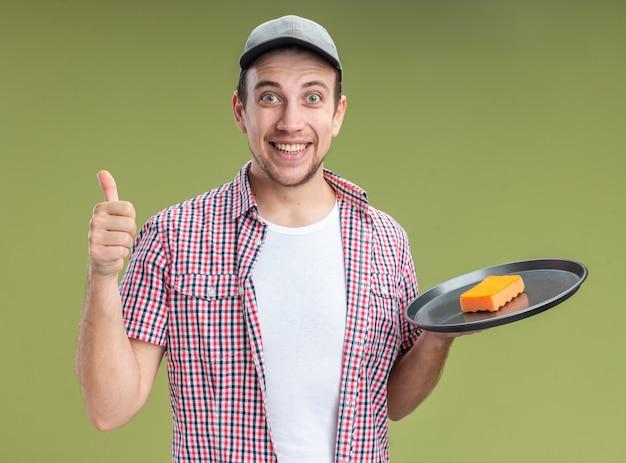 オリーブグリーンの壁に分離された親指を示すトレイにスポンジを保持しているキャップを身に着けている若い男クリーナーの笑顔