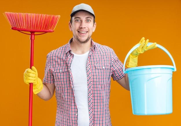 Улыбающийся молодой парень уборщик в кепке с перчатками держит ведро и швабру, изолированные на оранжевой стене
