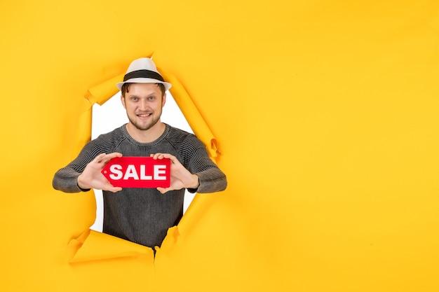 젊은 남자가 들고 웃고 노란색 벽에 찢어진 판매 사인을 보여주는