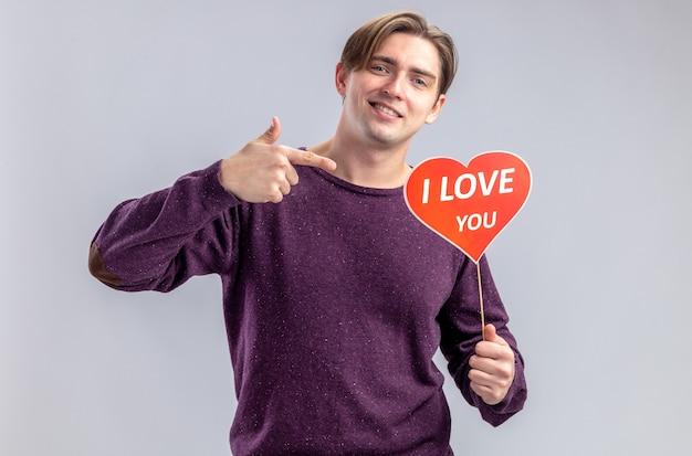 バレンタインデーの保持と白い背景で隔離のテキストを愛して棒で赤いハートを指す笑顔の若い男