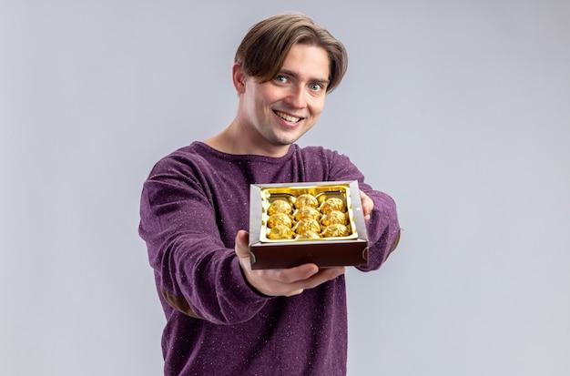 Улыбающийся молодой парень в день святого валентина, протягивая коробку конфет перед камерой, изолированной на белом фоне
