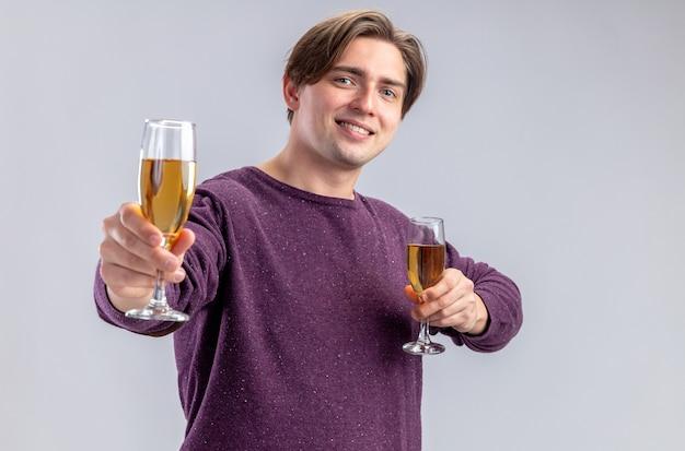 白い背景で隔離のカメラでシャンパンのグラスを差し出してバレンタインデーに笑顔の若い男