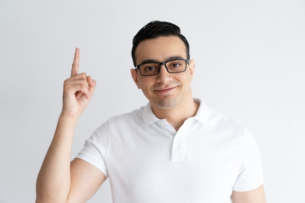 Smiling young guy pointing upwards and looking at camera.