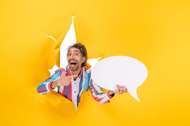 黄色い紙の引き裂かれた穴に空きスペースのある白いページを指す笑顔の若い男