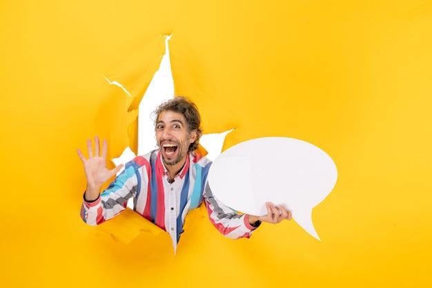 Giovane ragazzo sorridente che indica la pagina bianca con spazio libero e mostra cinque in un buco strappato in carta gialla yellow