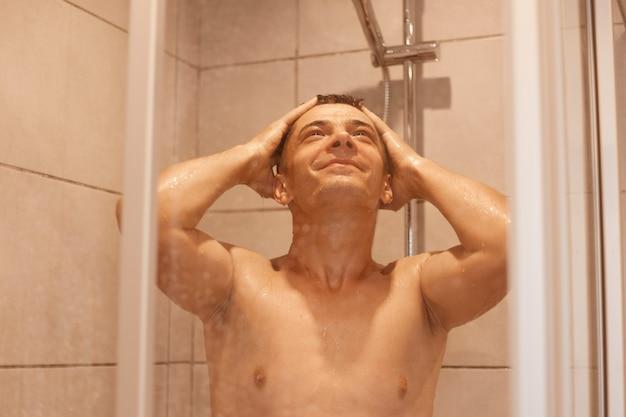 웃고 있는 젊은 남자는 새로운 날을 시작하고, 샤워를 하고, 떨어지는 물방울 아래 서서, 벗은 몸을 씻고, 집에 있는 욕실에서 머리를 합니다. 남성 바디 케어 및 일상적인 위생 루틴.