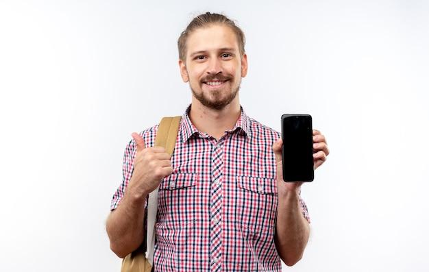 バックパックを持って電話でポイントを身に着けている若い男の学生の笑顔