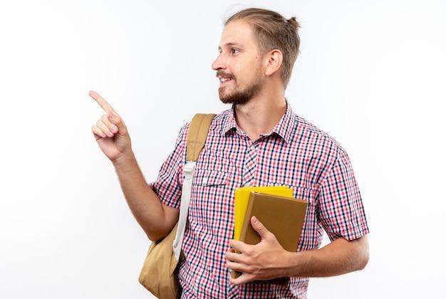 コピースペースと白い壁に分離された側に本のポイントを保持しているバックパックを身に着けている若い男の学生の笑顔