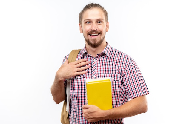 Sorridente giovane studente che indossa uno zaino in possesso di libri mettendo la mano su se stesso isolato su muro bianco