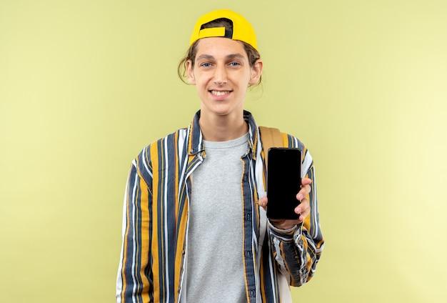 オリーブグリーンの壁に分離された電話を保持しているキャップとバックパックを身に着けている若い男の学生の笑顔