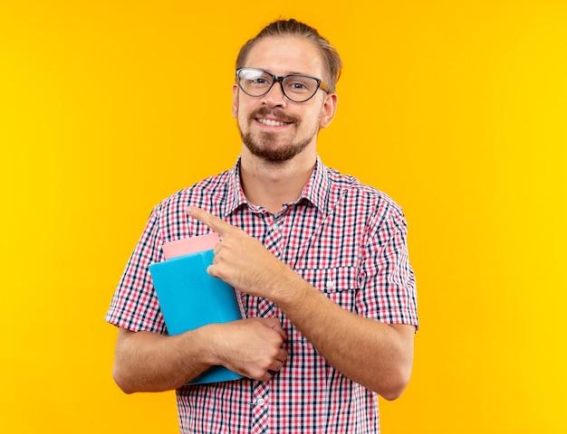 Sorridente giovane studente che indossa uno zaino con gli occhiali che tengono i punti del libro sul lato isolato sulla parete arancione con spazio per le copie