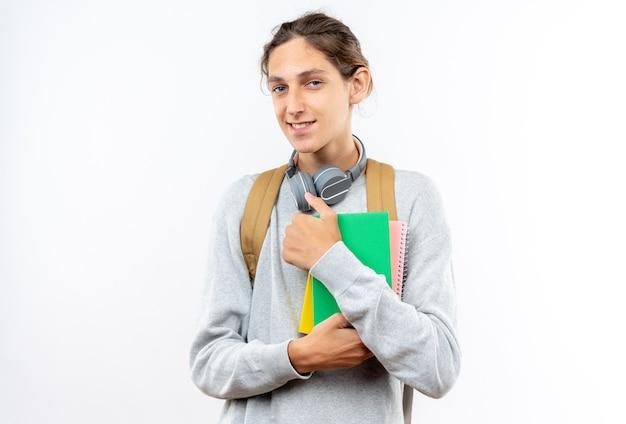 Sorridente giovane studente che indossa uno zaino con le cuffie sul collo che tiene libri isolati sul muro bianco