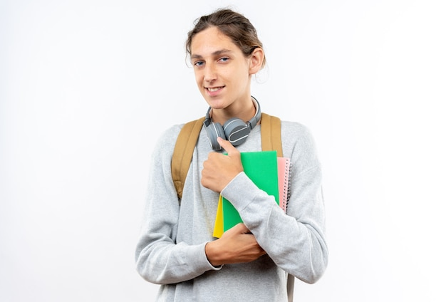 白い壁で隔離の本を保持している首にヘッドフォンでバックパックを身に着けている若い男の学生の笑顔