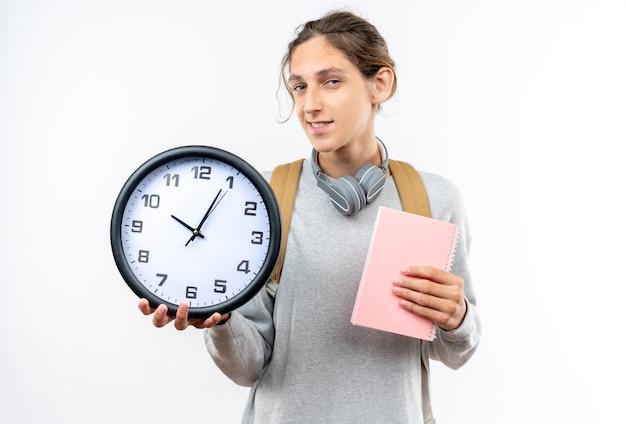 白い壁に分離されたノートブックと壁時計を保持している首にヘッドフォンとバックパックを身に着けている若い男の学生の笑顔