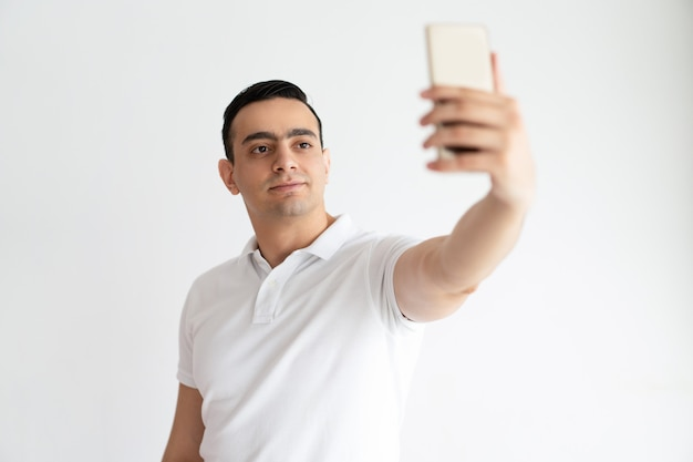 Smiling young guy taking selfie photo on smartphone. indian man using digital device.