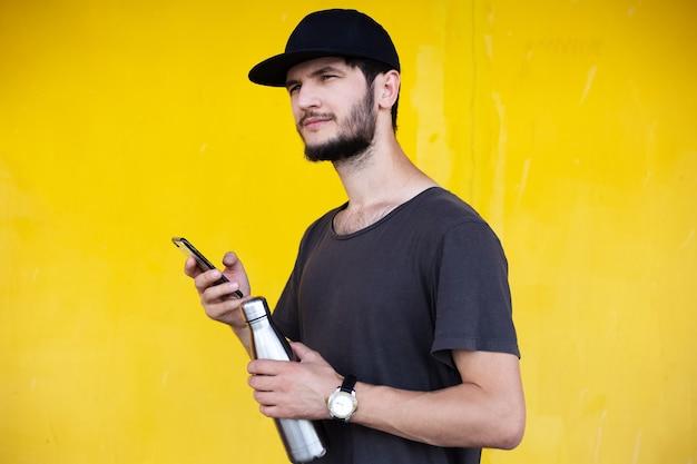 다른 손에 강철 보온병으로 스마트 폰을 사용하여 웃는 젊은 남자