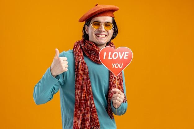 Sorridente giovane ragazzo il giorno di san valentino che indossa cappello con sciarpa e occhiali che tengono cuore rosso su un bastone con ti amo testo che mostra pollice in su isolato su sfondo arancione