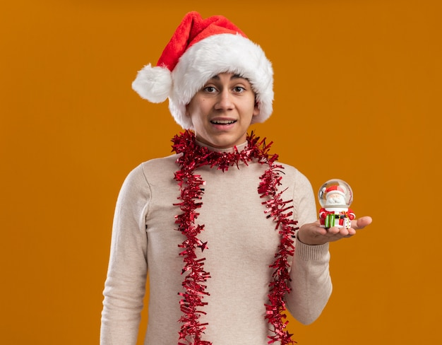 Smiling young guy wearing christmas hat with garland on neck holding christmas toy isolated on yellow background