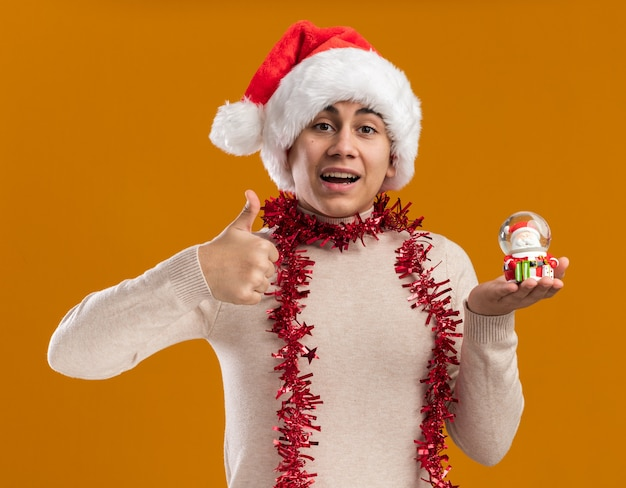 Smiling young guy wearing christmas hat with garland on neck holding christmas toy showing thumb up isolated on yellow wall