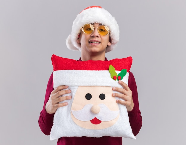 Smiling young guy wearing christmas hat with glasses holding christmas pillow isolated on white background