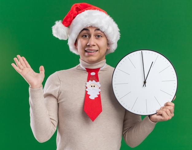 Улыбающийся молодой парень в рождественской шляпе с галстуком держит настенные часы, протягивая руку, изолированную на зеленой стене