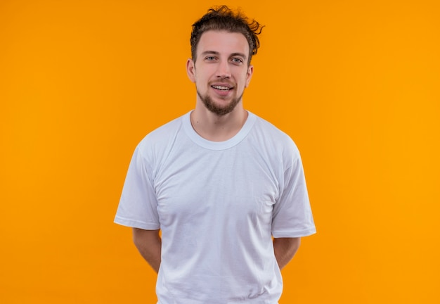 Smiling young guy wearing white t-shirt put his hand on back on isolated orange background
