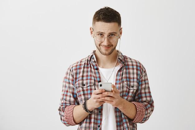 彼の携帯電話とイヤホンでポーズをとってメガネで若い男に笑顔