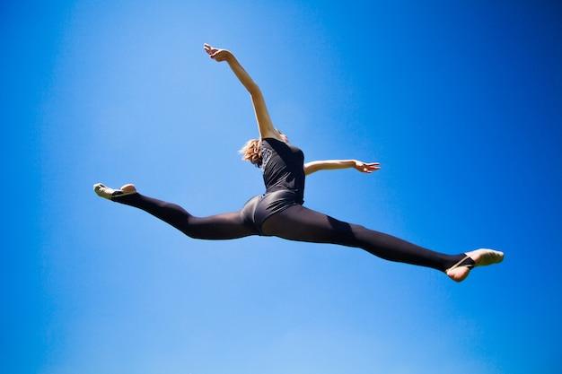 Улыбающийся юный гимнаст прыгает в шпагате и парит над землей.