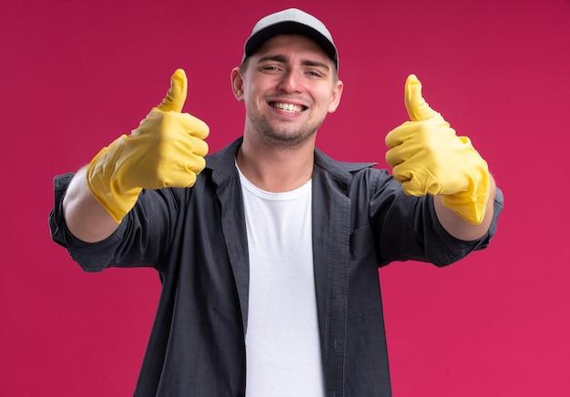 ピンクの壁に分離された親指を示す手袋とtシャツとキャップを身に着けている若い厄介な掃除人の笑顔