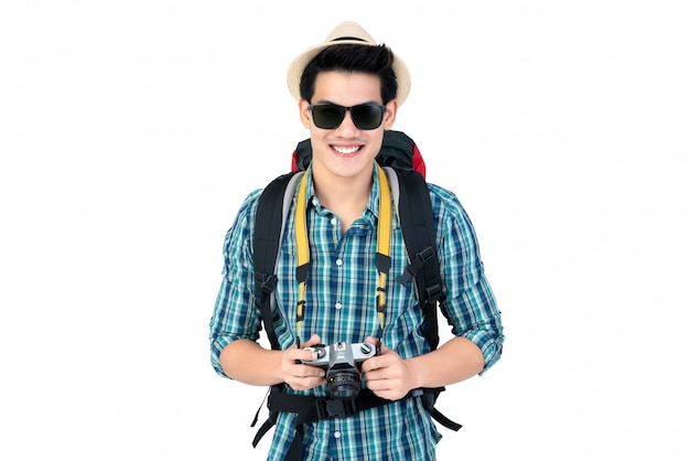 Smiling young handsome asian tourist man carrying backpack and holding camera