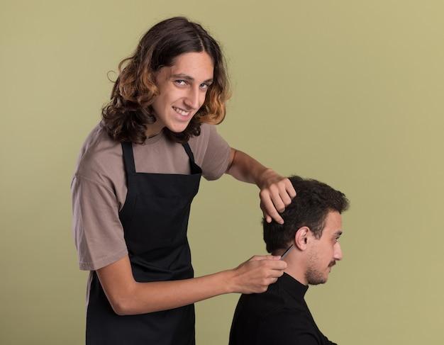 Sorridente giovane barbiere bello che indossa l'uniforme che fa taglio di capelli per il suo giovane cliente