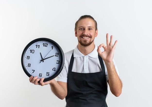 Sorridente giovane barbiere bello che indossa l'orologio uniforme della holding e facendo segno giusto isolato sulla parete bianca