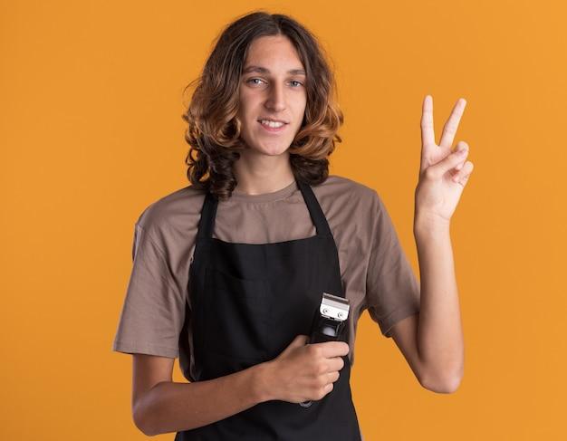 平和のサインをしているバリカンを保持している制服を着ている若いハンサムな床屋の笑顔