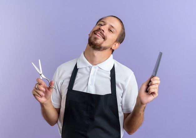 紫色の壁に分離されたはさみと櫛を保持している制服を着て若いハンサムな床屋の笑顔