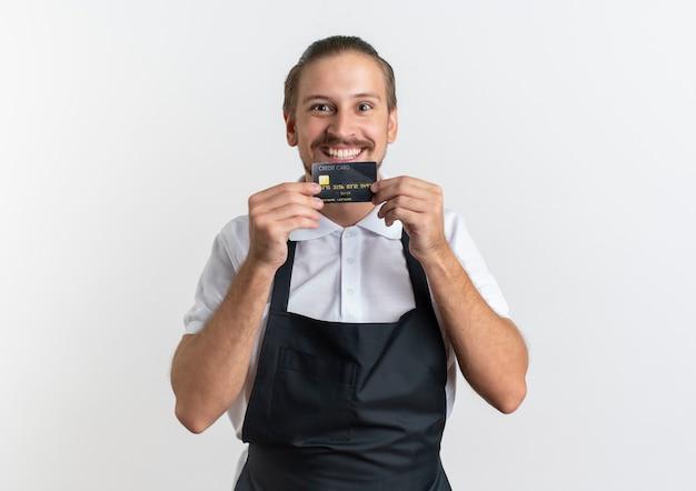 Улыбающийся молодой красивый парикмахер в униформе показывает кредитную карту, изолированную на белой стене