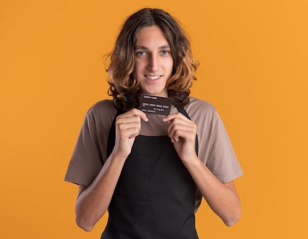 オレンジ色の壁に分離されたカメラにクレジットカードを示す制服を着て若いハンサムな理髪師の笑顔