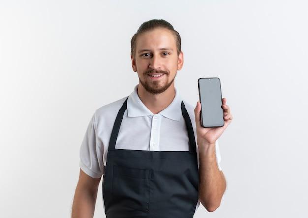 흰 벽에 고립 된 휴대 전화를 보여주는 유니폼을 입고 웃는 젊은 잘 생긴 이발사