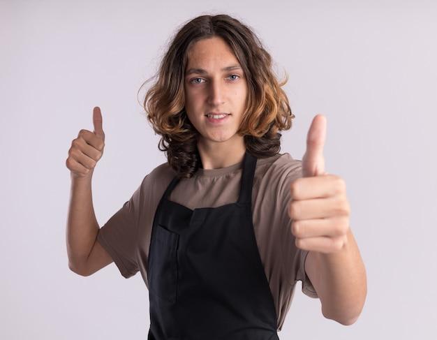 Sorridente giovane barbiere bello che indossa l'uniforme che mostra i pollici in su