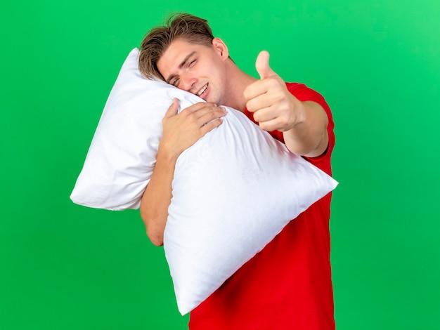 Sorridente giovane bella bionda uomo malato tenendo il cuscino che mette la testa sul cuscino guardando la telecamera che mostra il pollice in alto isolato su sfondo verde con copia spazio
