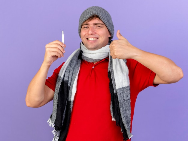 Smiling young handsome blonde ill man wearing winter hat and scarf holding thermometer looking at front showing thumb up isolated on purple wall