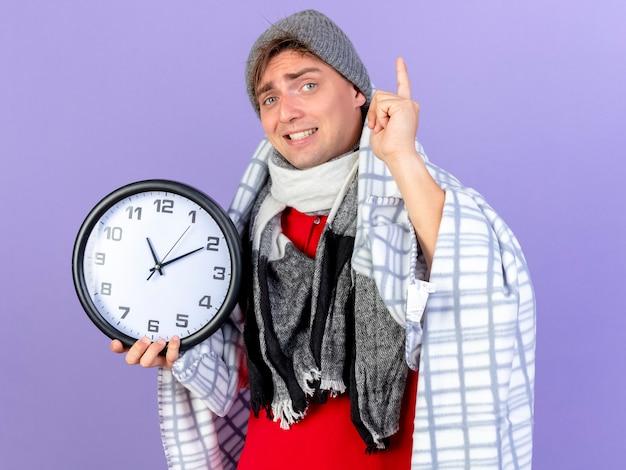 Sorridente giovane uomo malato biondo bello che indossa cappello invernale e sciarpa avvolta in un plaid tenendo l'orologio guardando la telecamera alzando il dito isolato su sfondo viola